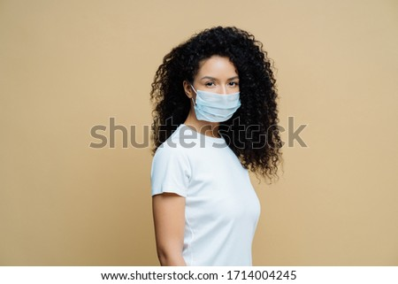 Sideways shot of Afro American woman wears protective face mask, protects against spread of coronavi Stock photo © vkstudio