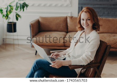 Sideways shot of woman entrepreneur sits in comfortable armchair in modern apartment with luxury fur Stock photo © vkstudio