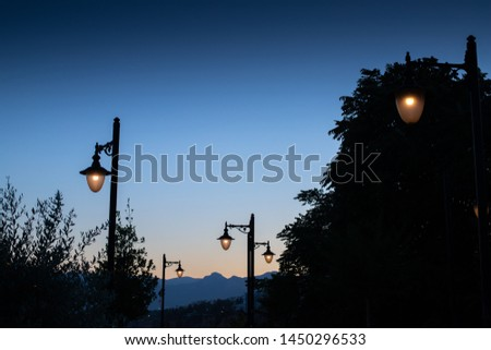 Lamp posts lit at night with blue mountain background at dusk Stock photo © jarenwicklund
