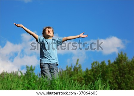 Boy standing with spreading hands on the field against the sky Stock photo © Paha_L