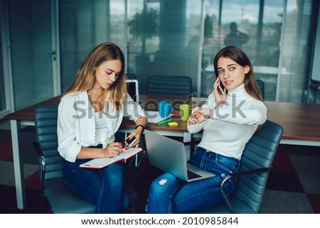 female executive using smartwatch while colleagues discussing on laptop in background stock photo © wavebreak_media