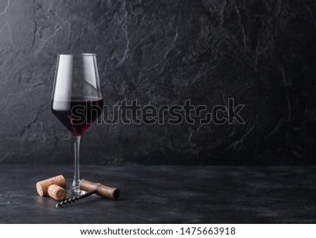 Elegant glass and bottle of red wine with corks on stone kitchen table background. Top view Stock photo © DenisMArt