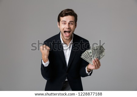 Image of joyous businessman 30s in formal suit holding copyspace Stock photo © deandrobot