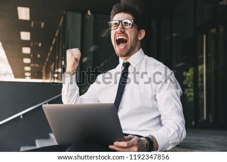 shocked business man near business center using laptop computer stock photo © deandrobot