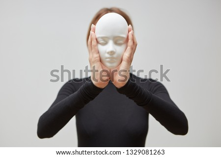 Plaster mask in the hand of young female instead face on a white background, place for text. Concept Stock photo © artjazz