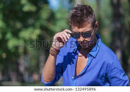 Attractive man holding his shades while looking down to a side Stock photo © feedough