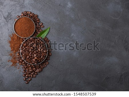 Stock photo: Fresh raw organic coffee beans with ground powder and cane sugar cubes with coffee trea leaf on blac