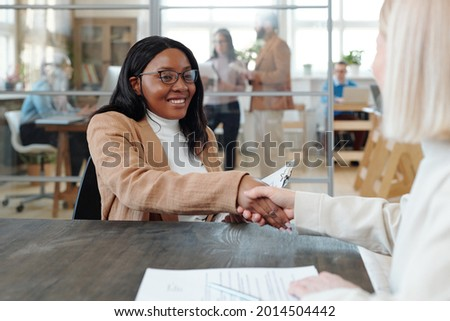 Happy young intercultural woman with eyeglasses in hands sitting in optics shop Stock photo © pressmaster