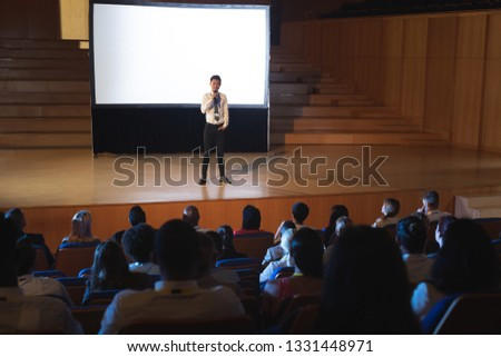 Front view of young Asian businessman speaking in front of business people sitting at business semin Stock photo © wavebreak_media