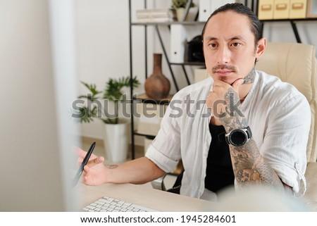 Grave masculina gráfico disenador mirando pantalla del ordenador Foto stock © pressmaster