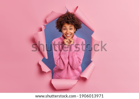 Lovely young African American woman grins at camera, keeps hand on rim of spectacles, glad to hear g Stock photo © vkstudio