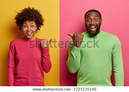 Image of pleased african american guy smiling and pointing finge Stock photo © deandrobot