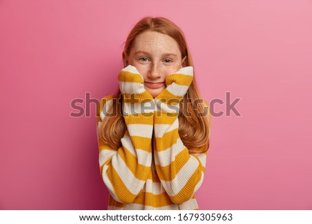 Portrait of cheerful female kid keeps hands under chin, has curlers on hair, going to have nice hair Stock photo © vkstudio