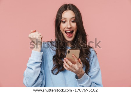 Image of delighted nice woman using cellphone and making winner gesture Stock photo © deandrobot