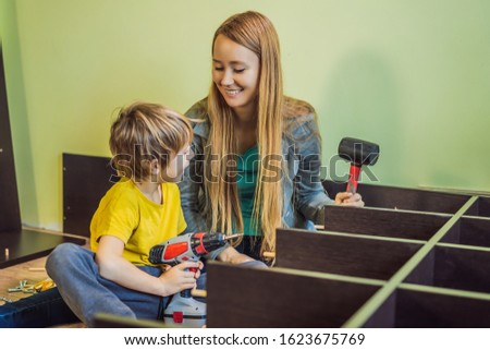 Mother and son assembling furniture. Boy helping his mom at home. Happy Family concept Stock photo © galitskaya