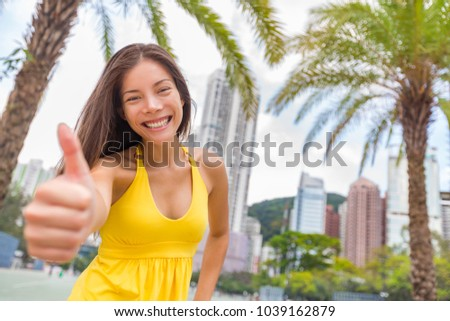 Happy chinese girl doing thumbs up in satisfaction in Hong Kong city, Asia China travel lifestyle. Y Stock photo © Maridav