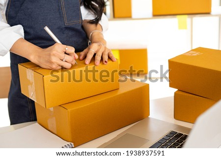 Asian man working sell online writing address on package of orde Stock photo © snowing