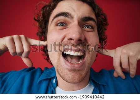 Image of stressed caucasian man screaming and plugging his ears Stock photo © deandrobot
