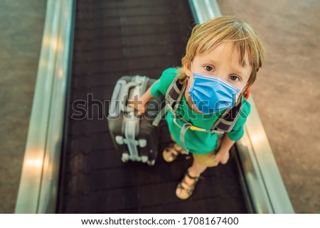 Funny little boy in medical mask going on vacations trip with suitcase at airport, indoors Tourists  Stock photo © galitskaya