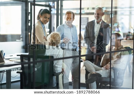Mature businessman explaining strategy to group of multiethnic b Stock photo © boggy