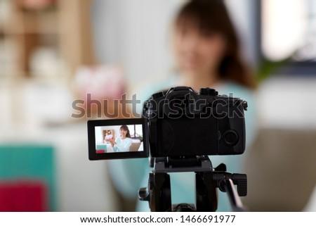 asian female blogger with gift bag recording video Stock photo © dolgachov