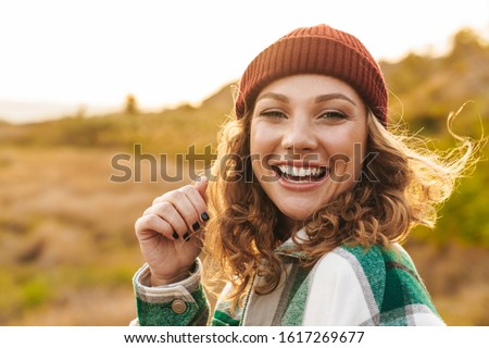 Image of young woman wearing hat and plaid shirt walking outdoor Stock photo © deandrobot
