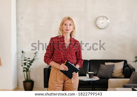 Blonde woman standing while holding notebooks against a white background Stock photo © wavebreak_media