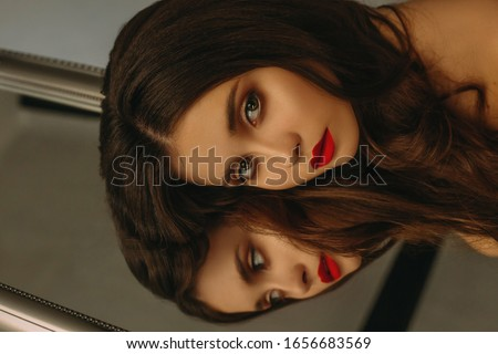 Portrait of a beautiful brunette near the luxury mirror (toned i Stock photo © Nejron