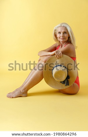 blonde woman posing while sitting on the floor looking at the ca Stock photo © feedough