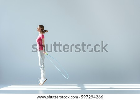 side view of sporty woman exercising with skipping rope on grey Stock photo © LightFieldStudios