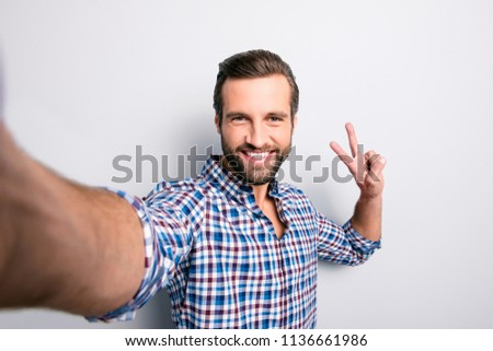 Picture of smiling bearded man in checkered shirt making selfie Stock photo © deandrobot