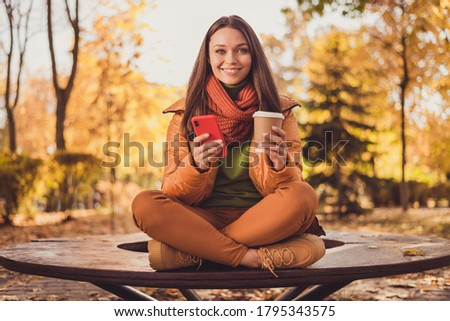 Young woman rests in autumn park on bench after a walk and liste Stock photo © boggy