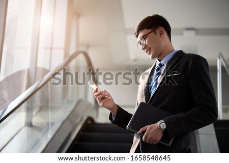 portrait of confident handsome elegant businessman holding credit card in his hand on black backgrou stock photo © traimak