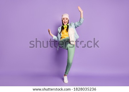 Image of beautiful woman wearing earphones rejoicing and holding Stock photo © deandrobot