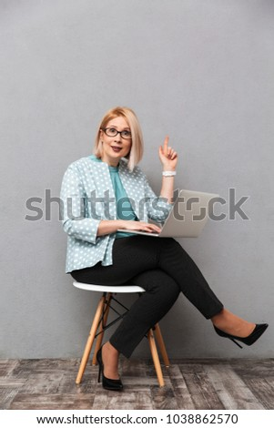 Business shocked woman posing isolated over grey wall background sitting at the table using laptop d Stock photo © deandrobot