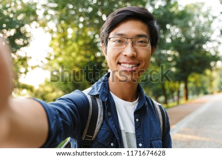happy asian male student in eyeglasses making selfie on smartphone stock photo © deandrobot