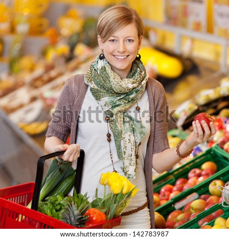 Happy casual woman with basket of fresh flowers looking at new sorts of petunias Stock photo © pressmaster