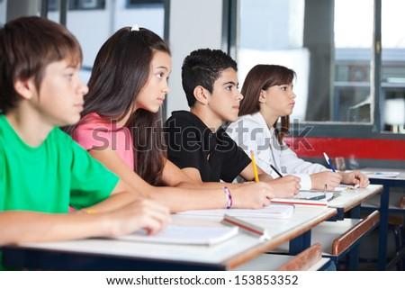 Vista lateral colegial sesión escritorio aula Foto stock © wavebreak_media