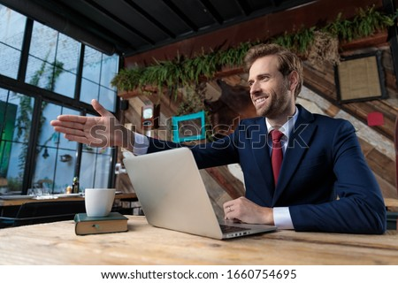 Happy young businessmen handshaking by the table in the office Stock photo © boggy