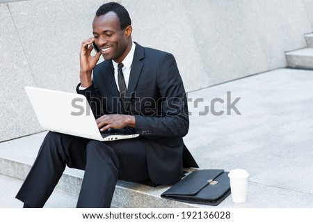 Side view of young African-American businessman with coffee cup using digital tablet in modern offic Stock photo © wavebreak_media