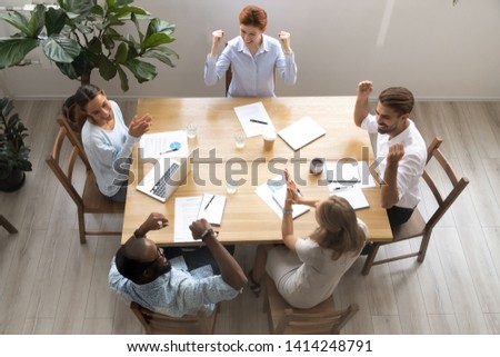 Top view of glad African American businesswoman smiles pleasantly, notes information, makes notes, w Stock photo © vkstudio