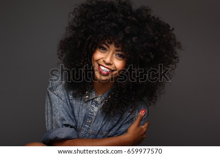 Front view of happy young African American woman with eyes closed playing with hair standing on the  Stock photo © wavebreak_media