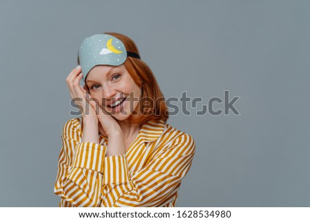 Morning and wake up. Cute cheerful redhead young European woman wears blindfold and nightwear, looks Stock photo © vkstudio