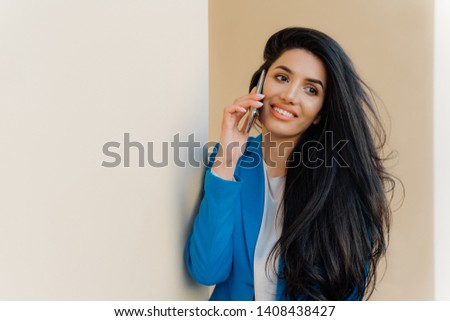 Happy young female student talks via cell phone after exam, shares her success. Brunette woman entre Stock photo © vkstudio