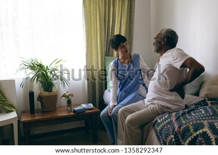 Front view of Asian female nurse talking with African-american senior man while walking with walker  Stock photo © wavebreak_media