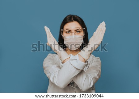 Woman wearing medical mask show stop gesture, crossed out sign with virus, flying virus pathogen Stock photo © robuart