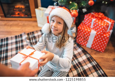 little girl takes christmas toys from the hands of mothers close up horizontal format stock photo © paha_l