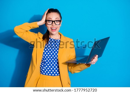 A woman with a laptop in her hands wearing glasses for vision stands near a gray wall Stock photo © ElenaBatkova