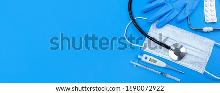 Medical face mask with white card and thermometer on blue background. Best protection from coronavir Stock photo © DenisMArt