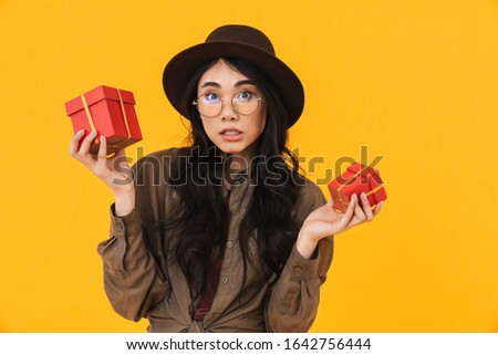 Image of asian woman hesitating while holding two birthday prese Stock photo © deandrobot